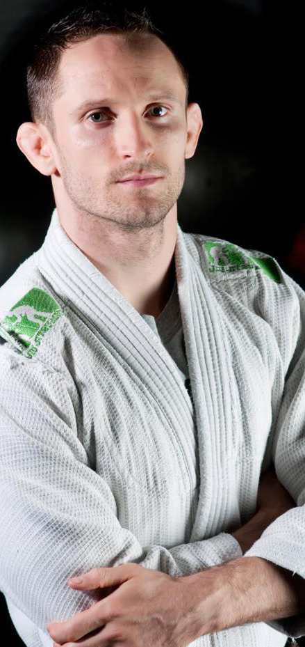 Timothy Hart in white BJJ Gi with green markings on shoulder